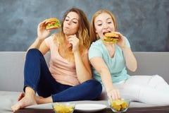 Duas jovens mulheres que comem avidamente hamburgueres e microplaquetas foto de stock royalty free