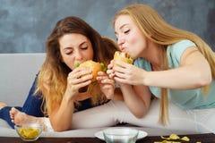 Duas jovens mulheres que comem avidamente hamburgueres e microplaquetas foto de stock