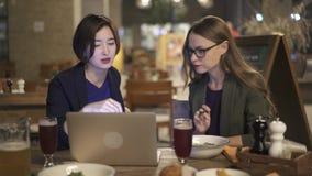 Duas jovens mulheres que discutem o projeto de trabalho e que comem no café na noite video estoque