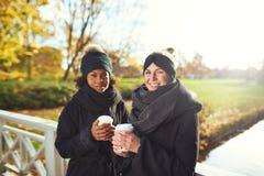 Duas jovens mulheres que estão na ponte e que guardam o café Foto de Stock Royalty Free