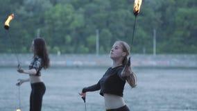 Duas jovens mulheres que executam uma mostra com as bolas da chama que estão no riverbank Artistas hábeis do fireshow que mostram vídeos de arquivo