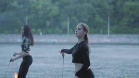 Duas jovens mulheres que executam uma mostra com as bolas da chama que estão no riverbank Artistas hábeis do fireshow que mostram video estoque