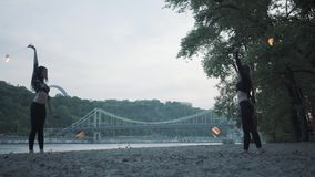 Duas jovens mulheres que executam uma mostra com as bolas da chama que estão no riverbank Mostrar fêmea dos artistas do fireshow  vídeos de arquivo