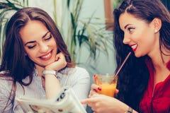 Duas jovens mulheres que falam e que leem o compartimento em um café imagem de stock