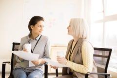 Duas jovens mulheres que falam na ruptura de café Imagens de Stock Royalty Free