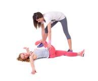 Duas jovens mulheres que fazem a ioga que estica exercícios Foto de Stock Royalty Free