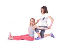 Duas jovens mulheres que fazem a ioga que estica exercícios Fotografia de Stock