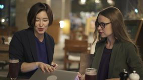 Duas jovens mulheres que fecham o portátil e que bebem a cerveja no café na noite vídeos de arquivo