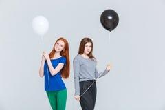 Duas jovens mulheres que guardam balões preto e branco imagem de stock royalty free