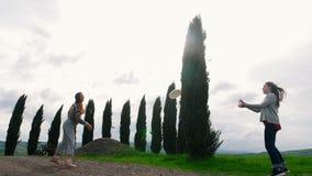 Duas jovens mulheres que jogam o frisbee em um campo verde em um fundo dos abeto filme