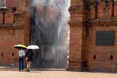 Duas jovens mulheres que levam guarda-chuvas amarelos e cor-de-rosa estão andando através do pulverizador de água instalado na po foto de stock royalty free