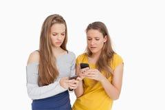 Duas jovens mulheres que olham de sobrancelhas franzidas ao olhar seus telemóveis Imagem de Stock
