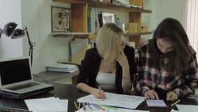 Duas jovens mulheres que olham o modelo, e usam a tabuleta no escritório filme