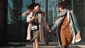 Duas jovens mulheres que perdem tempo e que têm o divertimento que anda na rua os amigos passam o tempo junto Movimento lento video estoque