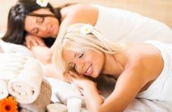 Duas jovens mulheres que relaxam no centro dos termas Foto de Stock