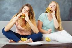Duas jovens mulheres que sentam-se no treinador que come o fast food foto de stock