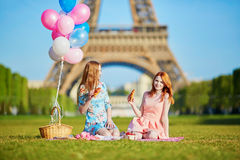 Duas jovens mulheres que têm o piquenique perto da torre Eiffel em Paris, França Foto de Stock