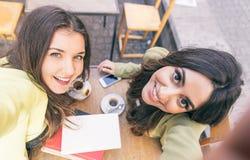 Duas jovens mulheres que tomam o selfie com telefone esperto fotos de stock