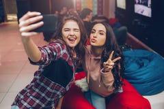 Duas jovens mulheres que tomam o selfie na câmera do telefone e que levantam em jogar a sala Eles dedos do shink e da mostra Mode foto de stock