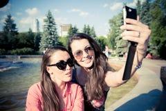 Duas jovens mulheres que tomam um selfie fora Imagem de Stock