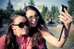 Duas jovens mulheres que tomam um selfie fora Fotografia de Stock