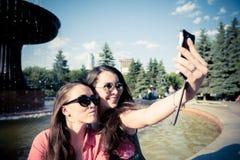 Duas jovens mulheres que tomam um selfie fora Fotos de Stock