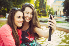Duas jovens mulheres que tomam um selfie fora Foto de Stock