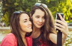 Duas jovens mulheres que tomam um selfie fora Fotografia de Stock Royalty Free