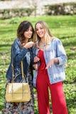 Duas jovens mulheres que usam o reconhecimento de voz do telefone exterior imagem de stock