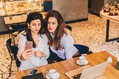 Duas jovens mulheres sentam-se em um café em uma tabela na frente de um portátil e fazem-se o selfie em um smartphone Encontrando Fotos de Stock Royalty Free