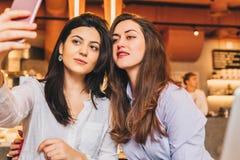 Duas jovens mulheres sentam-se em um café em uma tabela na frente de um portátil e fazem-se o selfie em um smartphone Encontrando Imagem de Stock Royalty Free