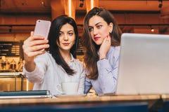 Duas jovens mulheres sentam-se em um café em uma tabela na frente de um portátil e fazem-se o selfie em um smartphone Encontrando Fotografia de Stock Royalty Free