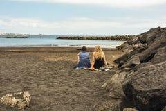 Duas jovens mulheres sentam-se na areia no oceano e falam-se Fotos de Stock Royalty Free