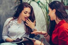 Duas jovens mulheres surpreendidas que falam e que bebem o café ao ler o compartimento foto de stock royalty free