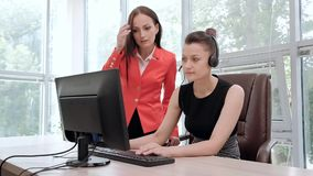 Duas jovens mulheres trabalham em um escritório brilhante no computador Discuta trabalhos e aprecie um negócio bem sucedido cabe? video estoque