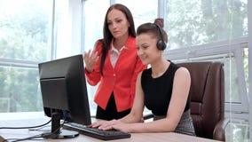 Duas jovens mulheres trabalham em um escritório brilhante no computador Discuta trabalhos e aprecie um negócio bem sucedido cabe? vídeos de arquivo