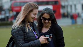 Duas jovens mulheres verificam fotos na câmera - Londres que sightseeing no movimento lento video estoque