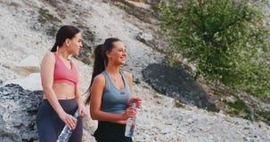 Duas jovens senhoras dos amigos que sorriem e que sentem excitadas após um dia duro do exercício têm uma ruptura no meio da surpr filme