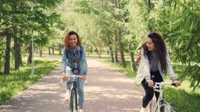 Duas jovens senhoras felizes estão dando um ciclo no parque e estão falando apreciando a natureza bonita e aquecem o dia ensolara vídeos de arquivo