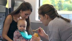 Duas jovens senhoras que alimentam um bebê no trem filme