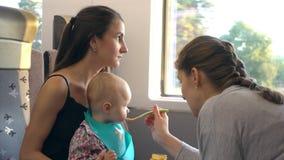 Duas jovens senhoras que alimentam um bebê no trem Imagem de Stock
