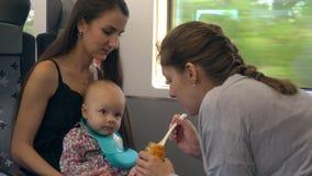 Duas jovens senhoras que alimentam um bebê no trem Fotografia de Stock