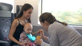 Duas jovens senhoras que alimentam um bebê no trem Fotos de Stock