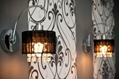 Duas lâmpadas de parede com papel de parede do design floral fotografia de stock royalty free