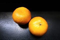 Duas laranjas em um fundo de madeira de superfície preto imagem de stock royalty free