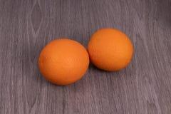 Duas laranjas situadas de lado a lado com uma estrutura de madeira fotos de stock royalty free
