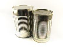 Duas latas de estanho brilhantes do alimento no fundo branco Imagem de Stock Royalty Free