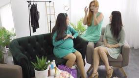 Duas lindas meninas em vestidos leves conversando com sua amiga grávida na sala de estar Mulheres acalmando vídeos de arquivo