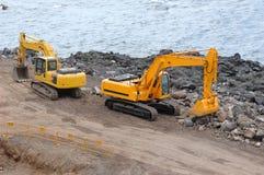 Duas máquinas escavadoras alaranjadas Foto de Stock Royalty Free