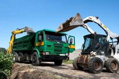 Duas máquinas escavadoras carregaram o descarregador Fotografia de Stock Royalty Free